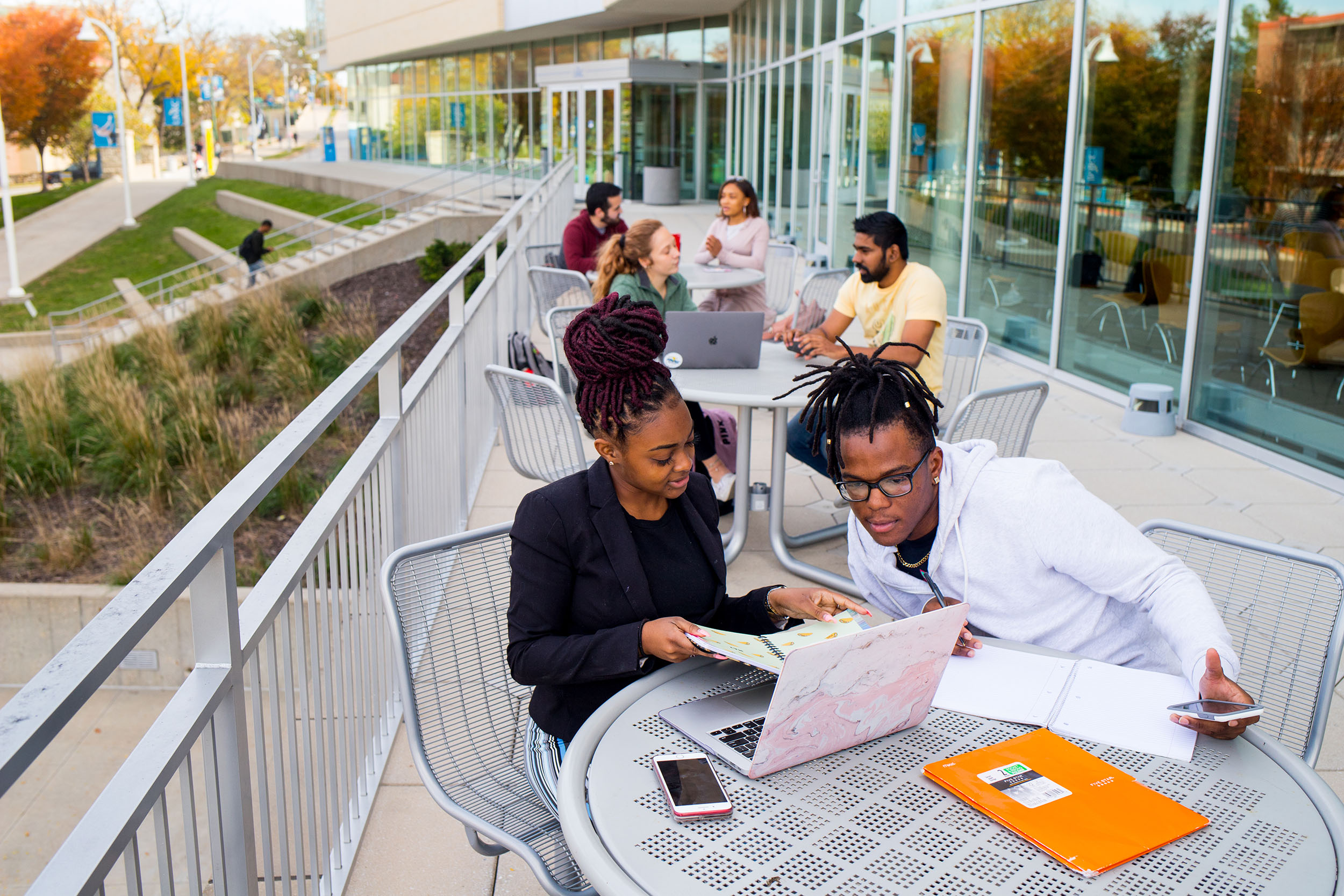 students looking at computer on patio