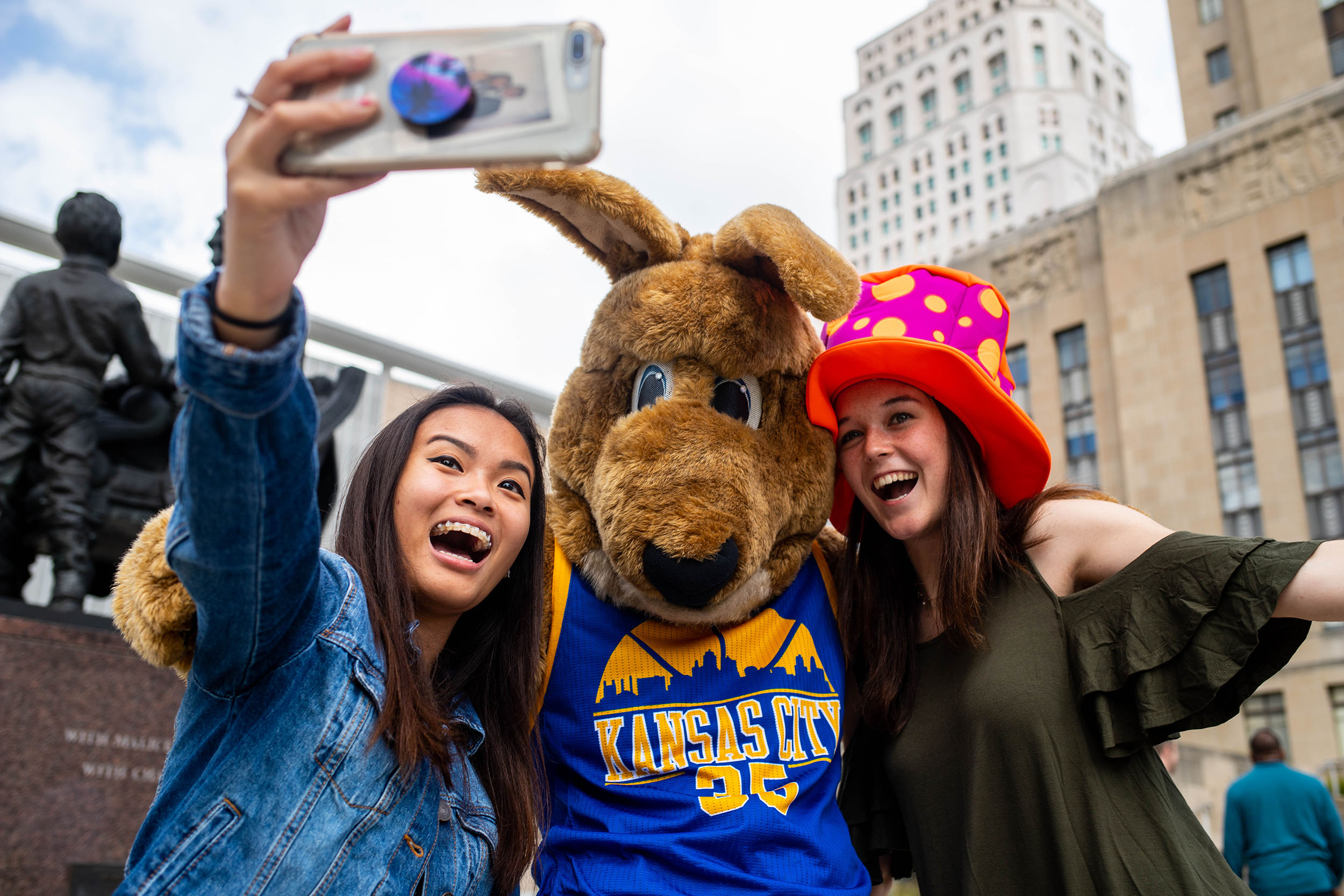 Two students pose with Kasey the UMKC kangaroo mascot