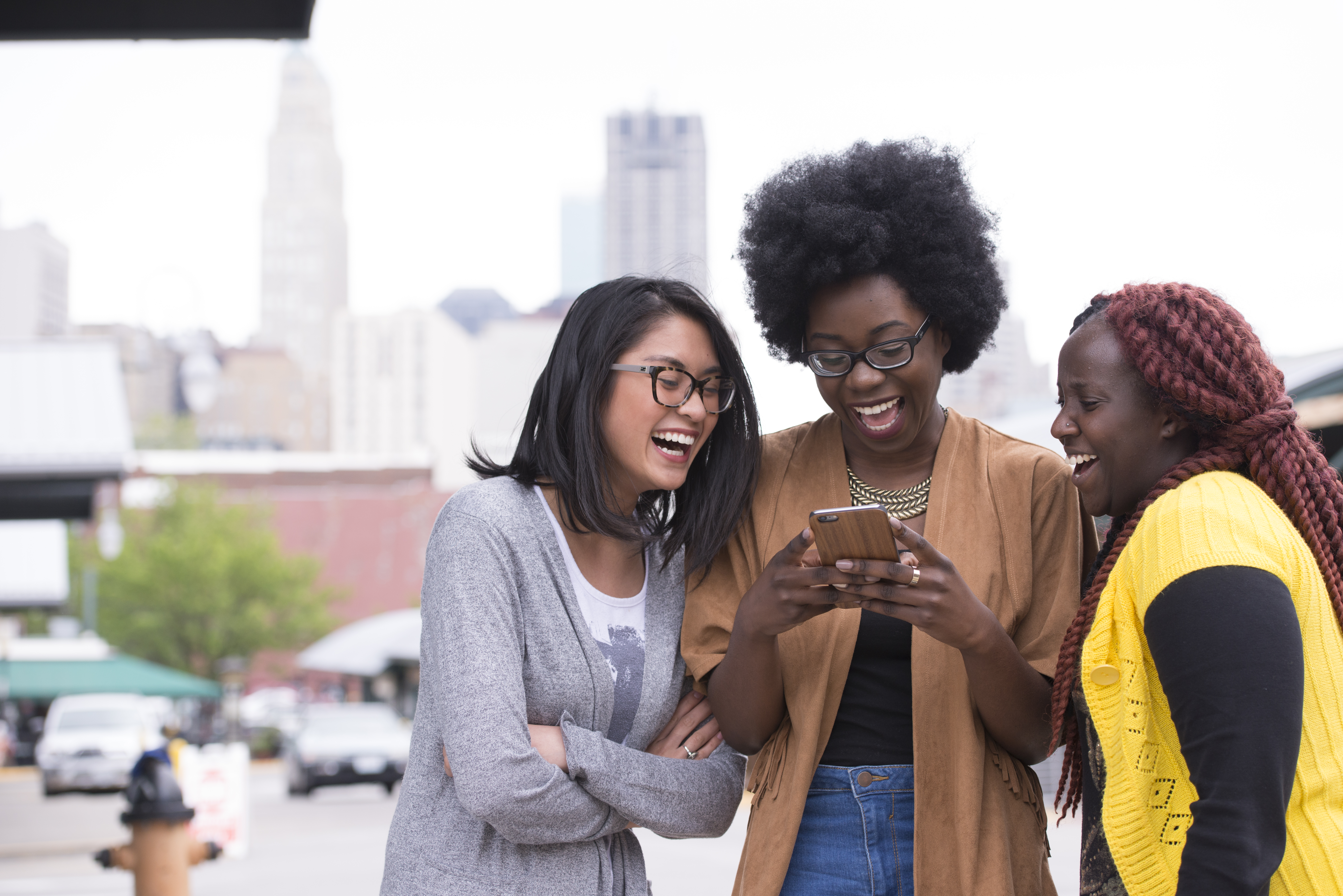 Three students look at phone and smile with Kansas City skyline in background