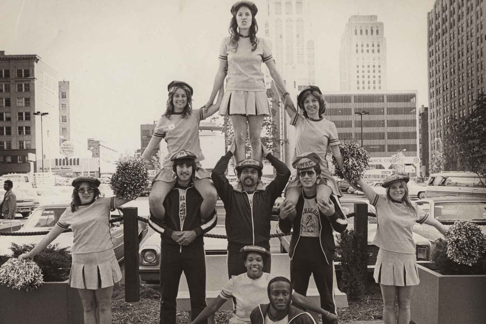 UMKC cheerleaders in black and white picture stand in a pyramid