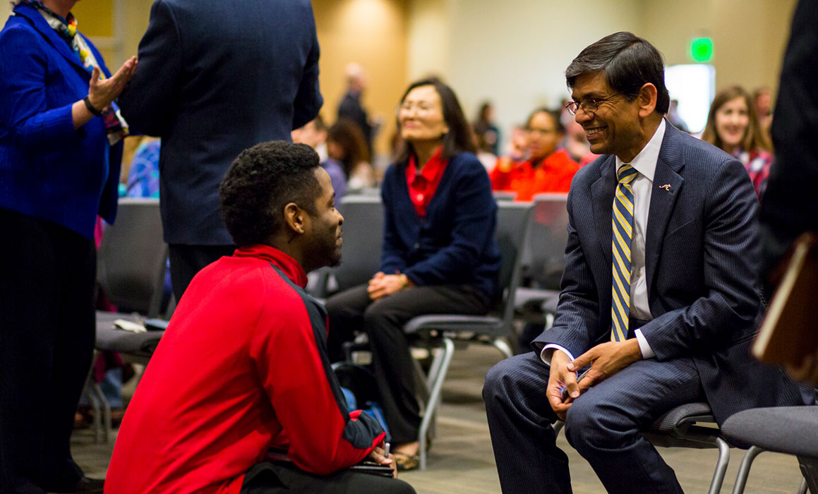 Student presenting as black male squats in front of seated and smiling Chancellor Agrawal