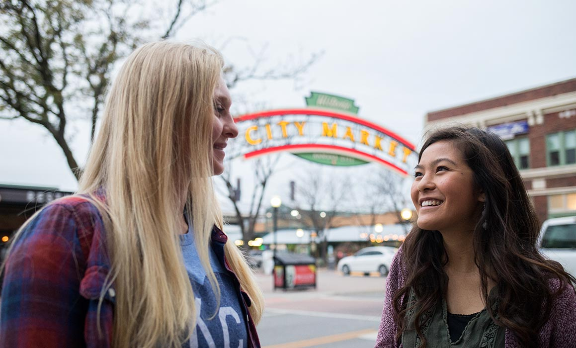 Two students presenting as women stand in front of City Market sign