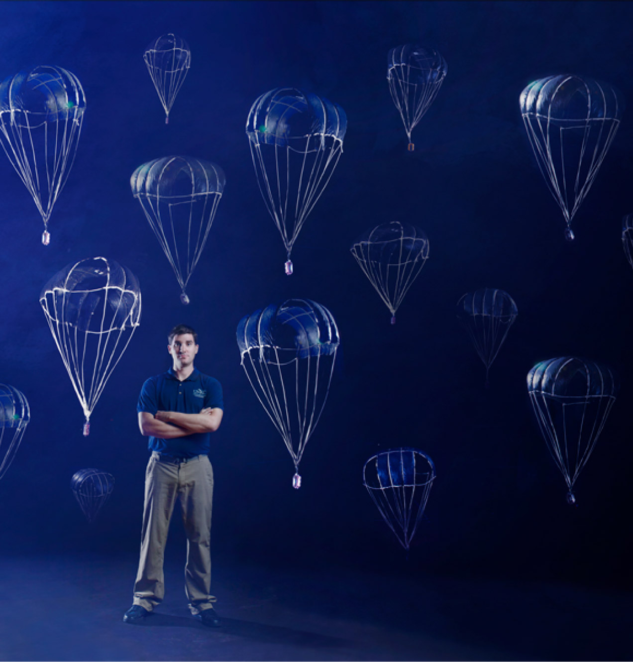 Researcher (presenting as white male) stands with arms crossed in front of dark background with white parachutes dropping items