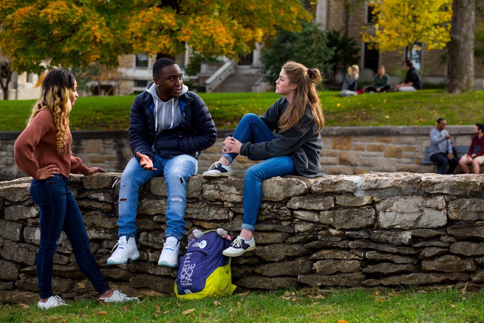 UMKC students sitting on a wall