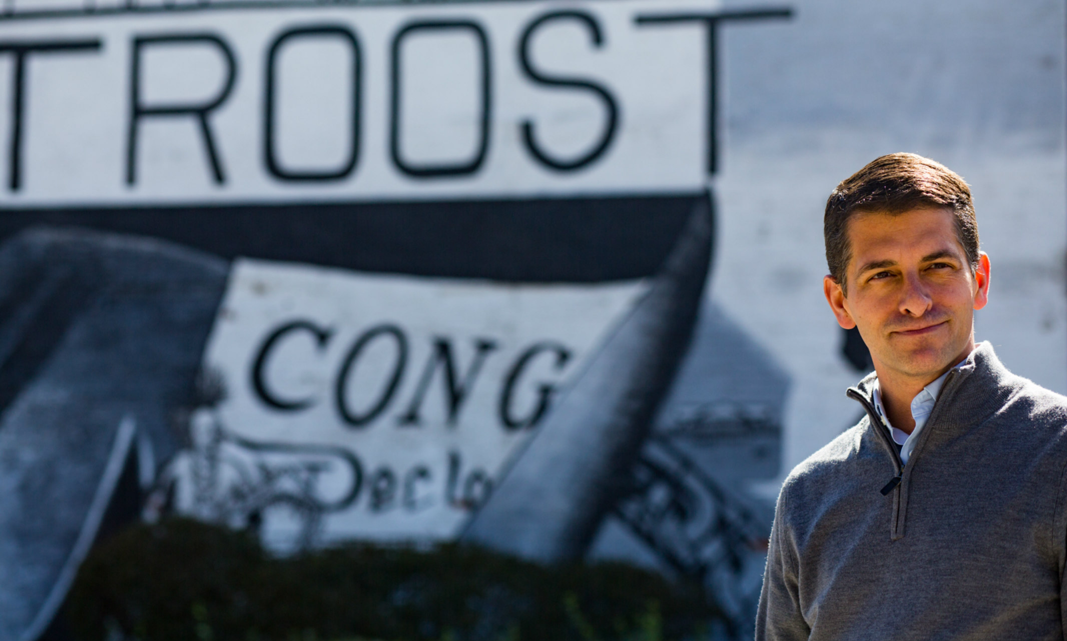 Brent Never stands in front of a mural on Troost Avenue.