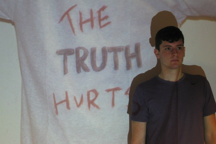 "A UMKC School of Medicine student stands in front of a screen that says ""The truth hurts."""