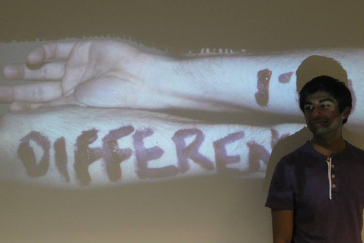 "A UMKC School of Medicine student stands in front of a screen that says ""different."""