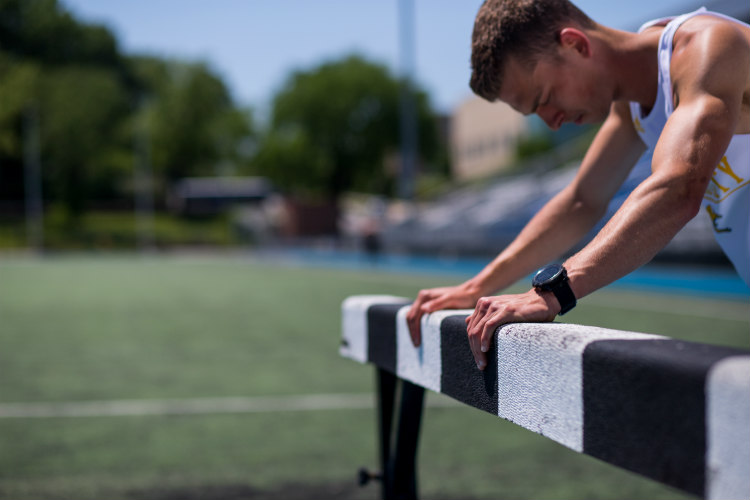 Bryce Miller stretching before jumping the hurdle