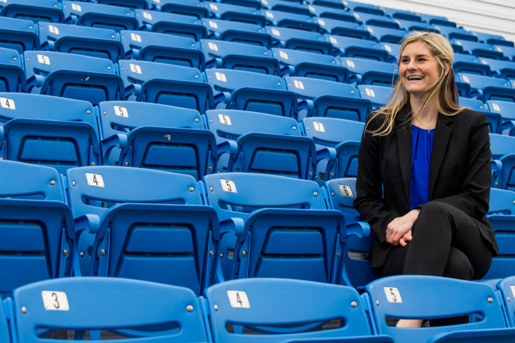 Anna Lillig sits in blue seats at Durwood Stadium at UMKC