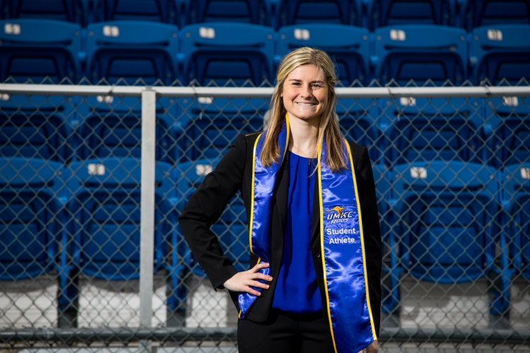 Anna Lillig stands in front of the blue seats of Durwood Stadium