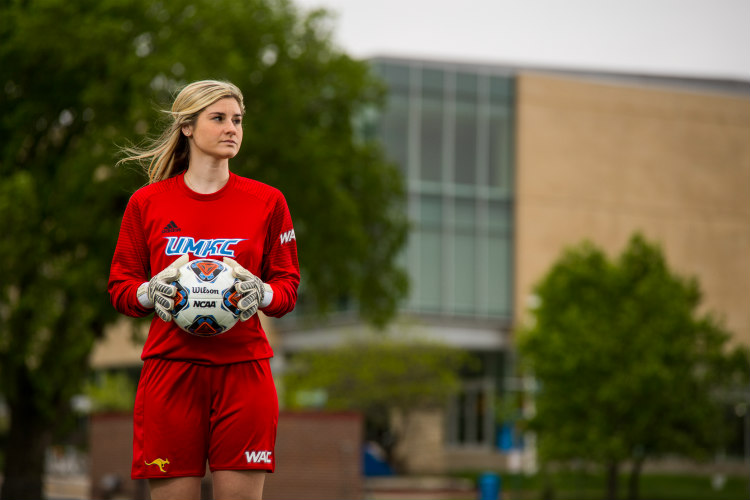 Anna Lillig stands wearing a UMKC goalkeeper uniform, holding a soccer ball