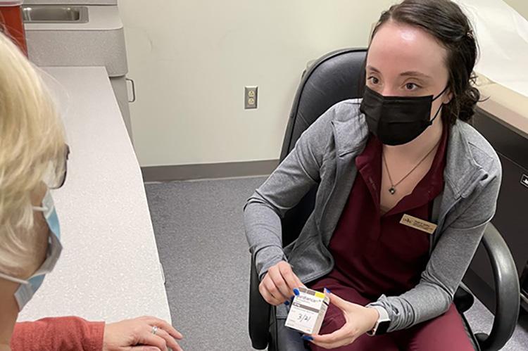 UMKC School of Pharmacy student Amelia Godfrey talks to a patient at Hannibal Free Clinic